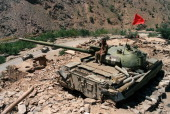 An Afghan soldier loyal to Soviet forces siting on a Sovietmade T64 tank watches 17 August 1989 around the valley near famous Salang Pass once a...