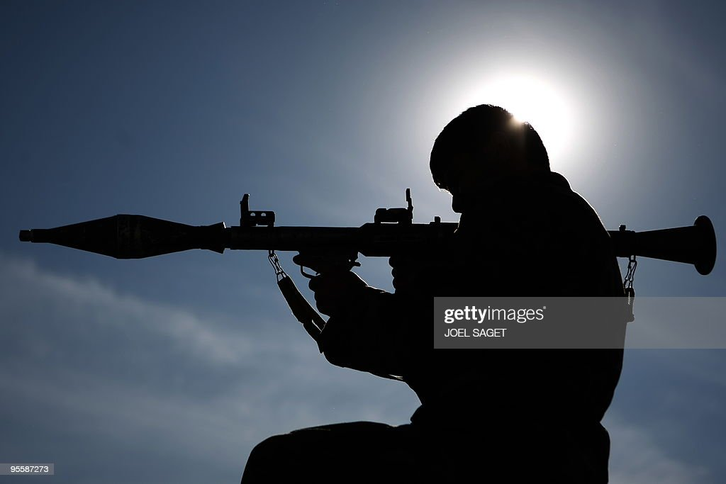An Afghan soldier poses with his rocket propelled grenade launcher at an 'Eagle's Nest' observation post in the Alah Say valley in Kapisa province on...
