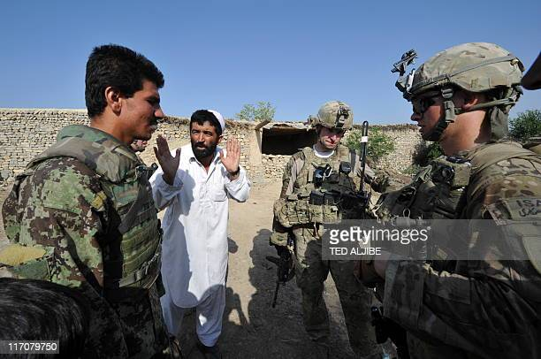 An Afghan soldier serves an interpreter as a civilian talks to US soldiers from Viper Company 126 Infantry during a patrol at a village near Combat...