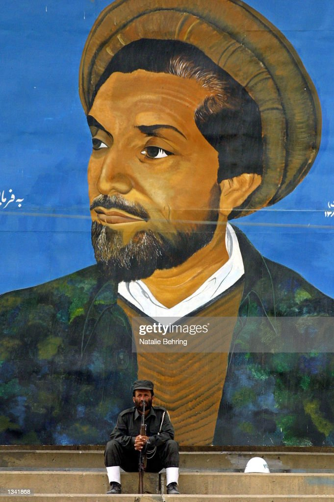 An Afghan soldier sits in front of a poster of slain Northern Alliance commander Ahmed Shah Masood August 18 2002 at Kabul's Olympic Stadium The...