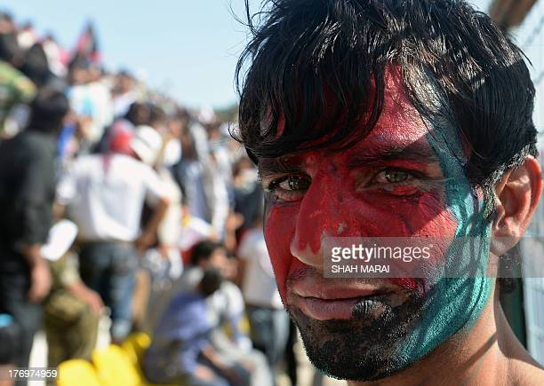 An Afghan spectators his face painted with the colours of the national flag poses during the match between Afghanistan and Pakistan at the...