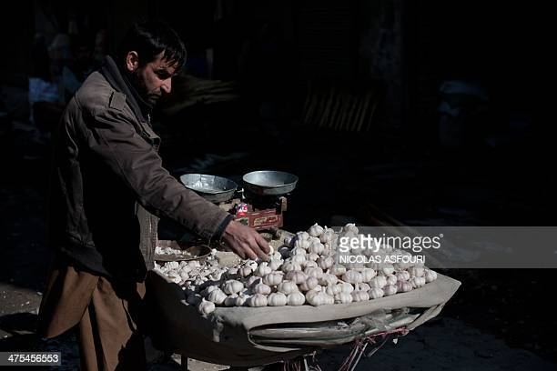 An Afghan street vendor sells garlic in Kabul on February 28 2014 Afghanistan's economy is recovering from decades of conflict but despite the...