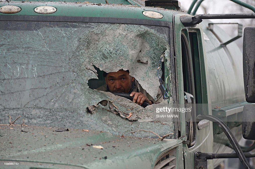 An Afghan truck driver peers through the broken windshield of his vehicle at the site of a suicide attack near the Afghan intelligence agency headquarters in Kabul on January 16, 2013. A squad of suicide bombers attacked the national intelligence agency headquarters in heavily-fortified central Kabul on January 16, killing at least two guards and wounding dozens of civilians, officials said. AFP PHOTO/ SHAH Marai