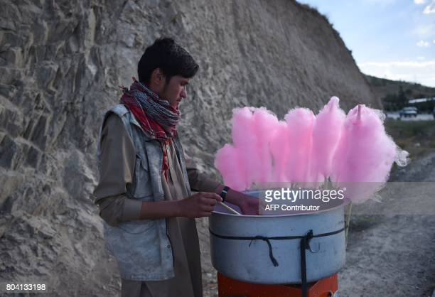 An Afghan vendor prepares cotton candy as he wait for costumers along a road near Qargha Lake on the outskirts of Kabul on June 30 2017 / AFP PHOTO /...