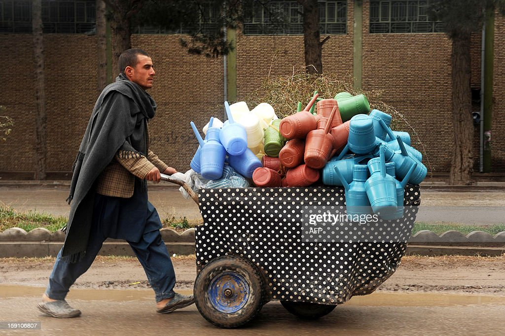An Afghan vendor sells plastic pots on a street in Herat on January 8 ,2013. Over a third of Afghans are living in abject poverty, as those in power are more concerned about addressing their vested interests rather than the basic needs of the population, a UN report said. AFP PHOTO/ Aref KARIMI