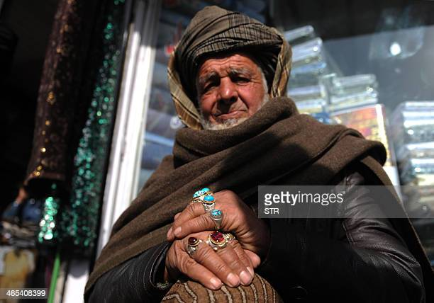 An Afghan vendor waits for customers as he tries to sell cloth in Kabul on January 27 2014 Economic development is considered a vital weapon to stop...