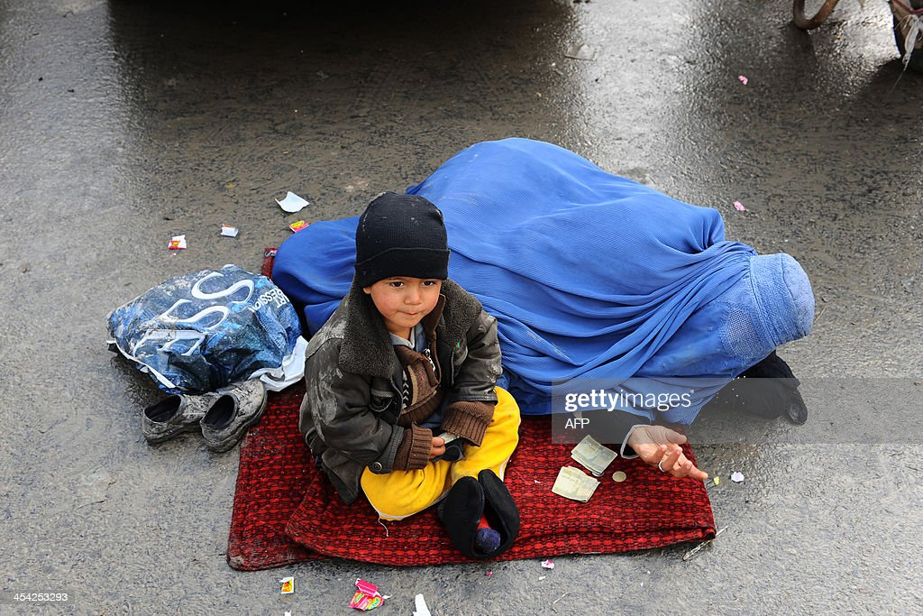 An Afghan woman and her child beg for alms on a street in Kabul on December 8, 2013. The UN mission in Afghanistan on Sunday criticised authorities for poor implementation of a landmark law to protect women, 12 years after the repressive Taliban regime was ousted from power. AFP PHOTO/Aref KARIMI