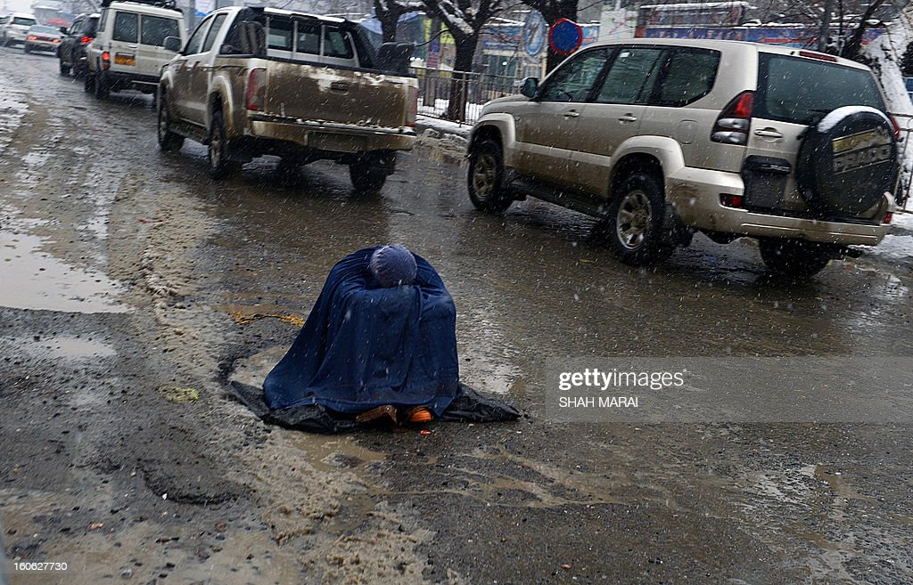 An Afghan woman begs for alms as she sits on a slush-filled road as snow falls in Kabul on February 4, 2013. As winter sets in across Central Asia, many Afghans struggle to provide adequate food and shelter for their families. AFP PHOTO/ SHAH Marai