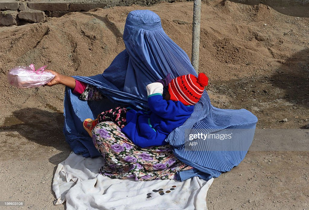 An Afghan woman begs in a street in Herat on November 24, 2012. The Afghan economy has always been based on agriculture, despite the fact that only 13 percent of its total land is arable and just eight percent is currently cultivated. AFP PHOTO/Aref KARIMI