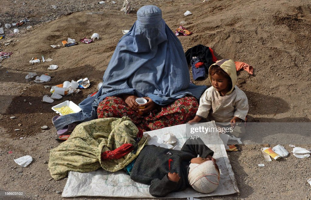 An Afghan woman begs with two children in a street in Herat on November 24, 2012. The Afghan economy has always been based on agriculture, despite the fact that only 13 percent of its total land is arable and just eight percent is currently cultivated. AFP PHOTO/Aref KARIMI