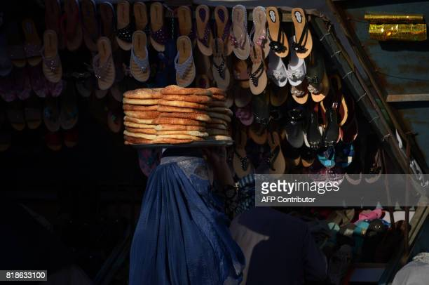 TOPSHOT An Afghan woman carries breads for sale on her head early in the morning in MazariSharif on July 19 2017 / AFP PHOTO / FARSHAD USYAN