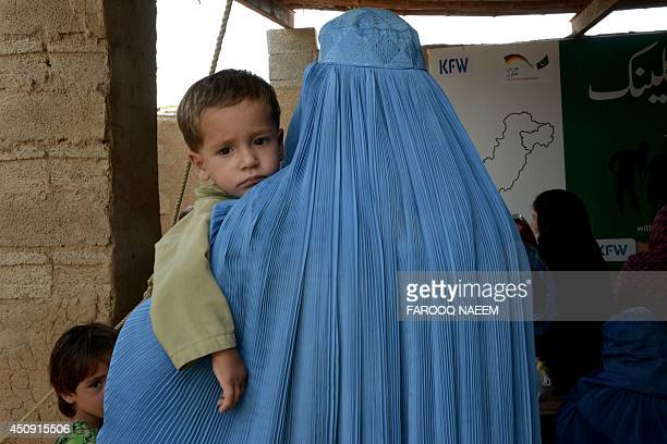 An Afghan woman carries her child as she arrives at a special medical camp organised by UNHCR with the coordination of Pakistan Medical Dental...