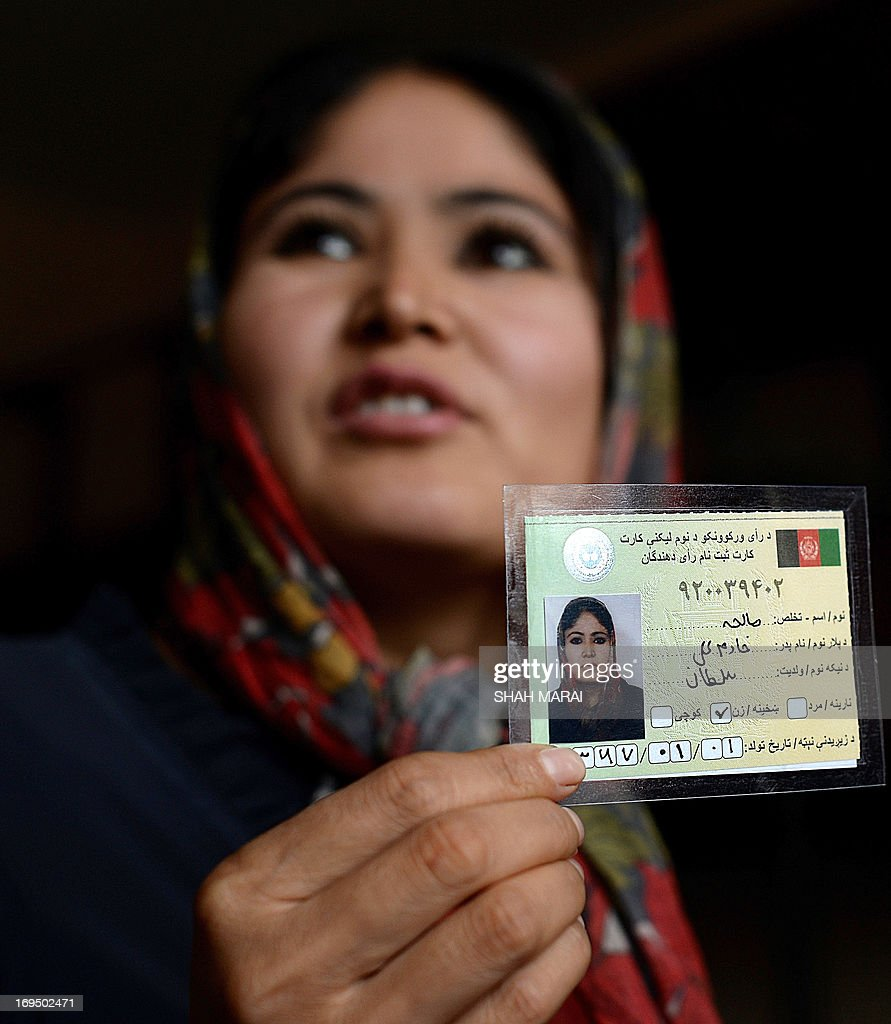An Afghan woman displays her voter registration card at an voter registration centre in Kabul on May 26, 2013. Afghanistan began registering voters on May 26 for elections to be held next year when NATO forces withdraw and leave the mammoth task of security to a tottering government amid growing insurgency. Registration began in 41 centres in all 34 provinces for those who have turned 18, previously not registered and those who have lost their old voter registration cards. AFP PHOTO/ SHAH Marai