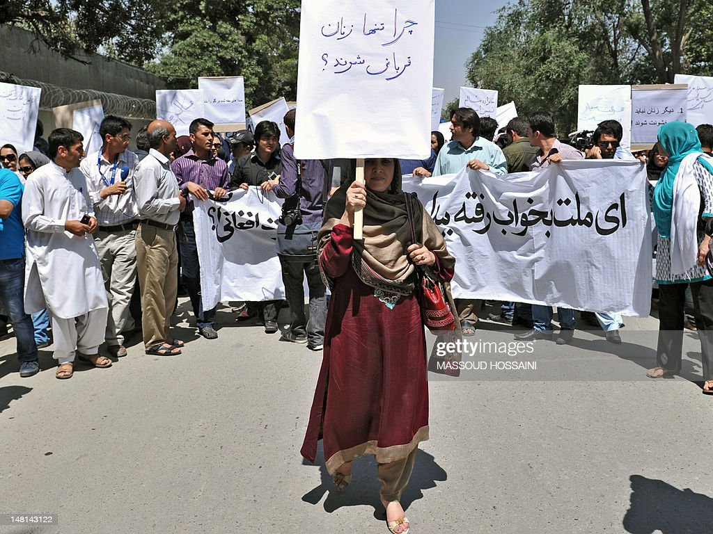 An Afghan woman, holding a placard which reads 'why just women are victims?', marches during a protest against the recent public execution of a young woman for alleged adultery, in Kabul on July 11, 2012. Dozens of Afghan women's rights activists took to the streets July 11 to protest the recent public execution of a young woman for alleged adultery, which was captured in ahorrific video. AFP PHOTO/Massoud HOSSAINI
