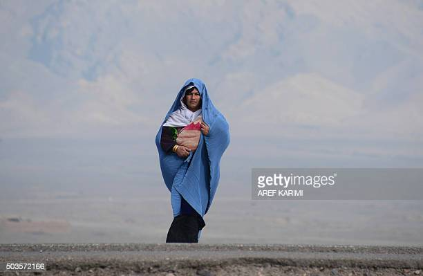 An Afghan woman holding her child waits for transportation on the outskirts of Herat on January 6 2016 AFP PHOTO / Aref Karimi / AFP / Aref Karimi