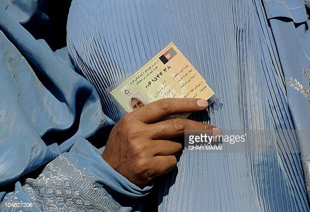 An Afghan woman holds her identification card as she lines up to cast her vote outside a polling station in Kabul on September 18 2010 Afghanistan...