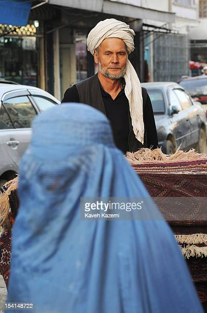 An Afghan woman in blue burka passes by a typically dressed man in head turban and garment transporting rugs on a push cart in Chicken Street on...