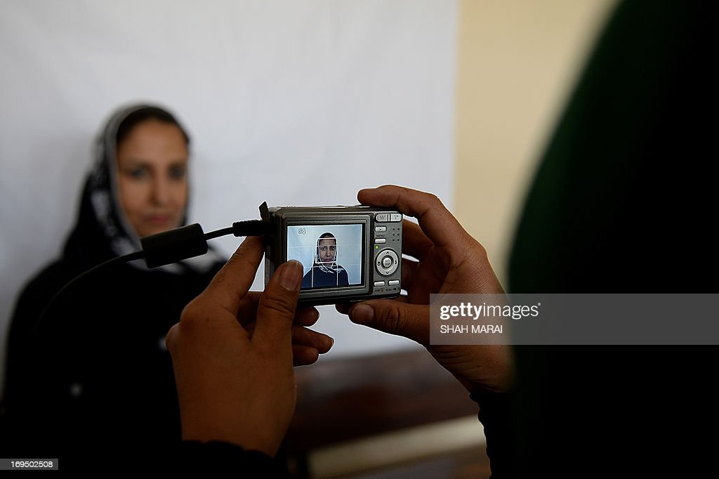 An Afghan woman poses for a photograph for identification purposes at a voter registration centre in Kabul on May 26, 2013. Afghanistan began registering voters on May 26 for elections to be held next year when NATO forces withdraw and leave the mammoth task of security to a tottering government amid growing insurgency. Registration began in 41 centres in all 34 provinces for those who have turned 18, previously not registered and those who have lost their old voter registration cards. AFP PHOTO/ SHAH Marai