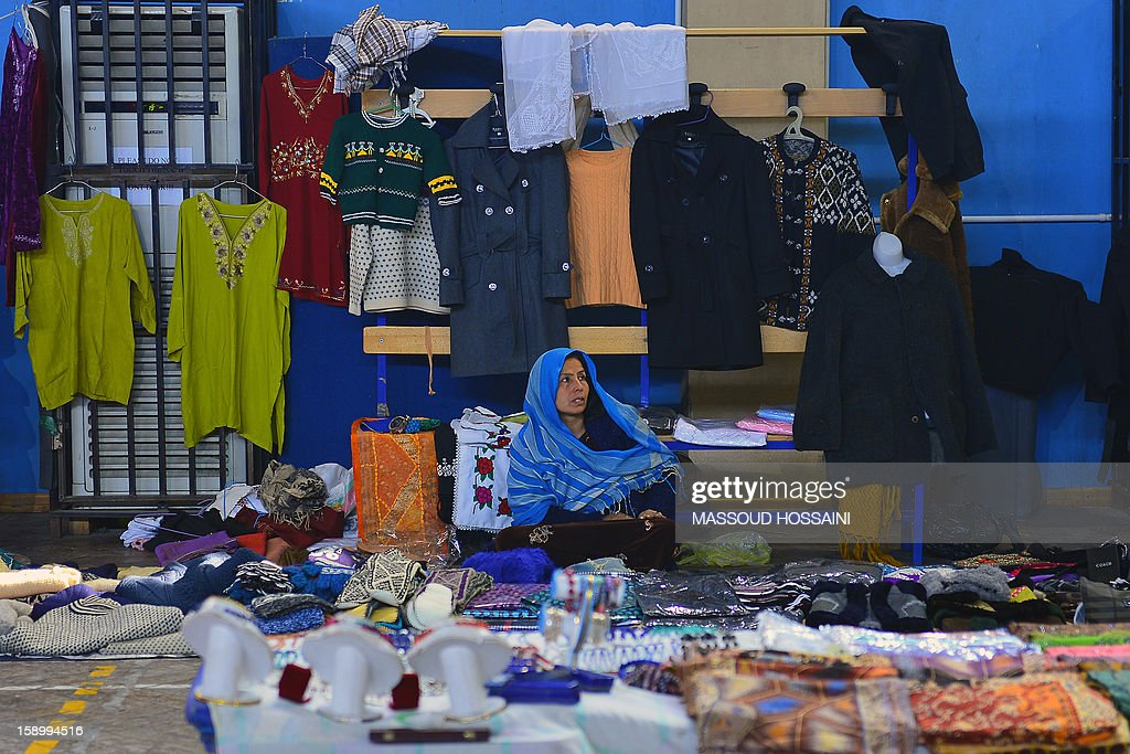 An Afghan woman sells clothing and handicraft items during a monthly bazaar at the International Security Assistance Force (ISAF) headquarters in Kabul on January 5, 2013. Analysts have warned the country could plunge into another large-scale civil war after the NATO-led force departs by 2015. AFP PHOTO / Massoud HOSSAINI