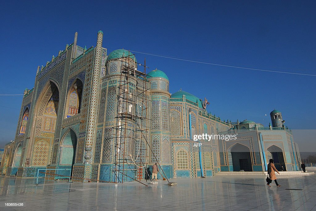 An Afghan woman (R) walks at the Ali Shrine in the northern town of Mazar-i-Sharif in Balkh province on March 14, 2013. Once known as the 'mother of cities,' the ancient city of Balkh was a popular destination along the ancient Silk Route. Balkh was destroyed by Mongol conqueror Genghis Khan during his rule, with the city's ruins remaining as a tourist attraction today. AFP PHOTO/Farshad Usyan