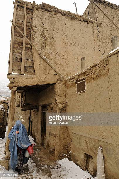 An Afghan woman walks through snow in an old district of Kabul on February 14 2008 More than 500 homes mostly traditional mud brick houses have been...