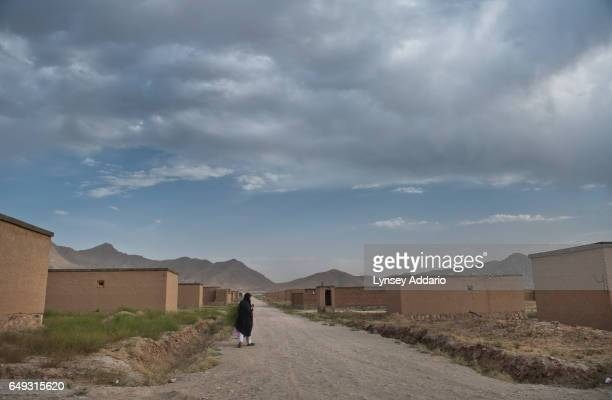 An Afghan woman walks through the mostly abandoned land allocation settlement of AliceGhan about 30 miles outside of Kabul Afghanistan July 22 2011