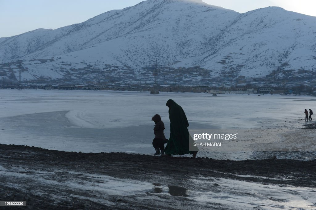 An Afghan woman walks with her daughter along Shuhada lake at sunset in Kabul on December 31, 2012. Over a third of Afghans are living in abject poverty, as those in power are more concerned about addressing their vested interests rather than the basic needs of the population, a UN report said. AFP PHOTO/ SHAH Marai