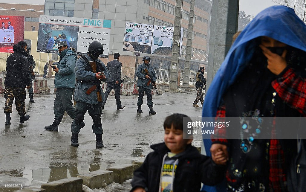 An Afghan woman with her child (R) move to safety as security personnel secure the site of a suicide attack near the Afghan intelligence agency headquarters in Kabul on January 16, 2013. A squad of suicide bombers attacked the national intelligence agency headquarters in heavily-fortified central Kabul on January 16, killing at least two guards and wounding dozens of civilians, officials said. AFP PHOTO/ SHAH Marai