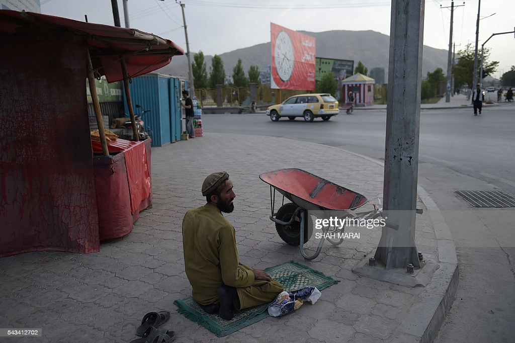 An Afghan worker prays next to his wheelbarrow prior to Iftar, the time to break fast during the Islamic month of Ramadan, in Kabul on June 28, 2016. Throughout the month, devout Muslims must abstain from food, drink and sex from dawn until sunset when they break the fast with the Iftar meal. / AFP / SHAH