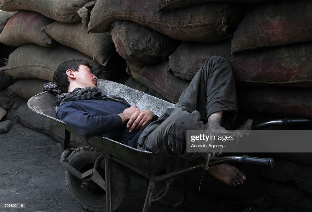 An Afghan worker sleeps on a wheelbarrow at a cotton factory as the world marks International Labor Day, also known as May Day in Kabul, Afghanistan, on May 1, 2016.