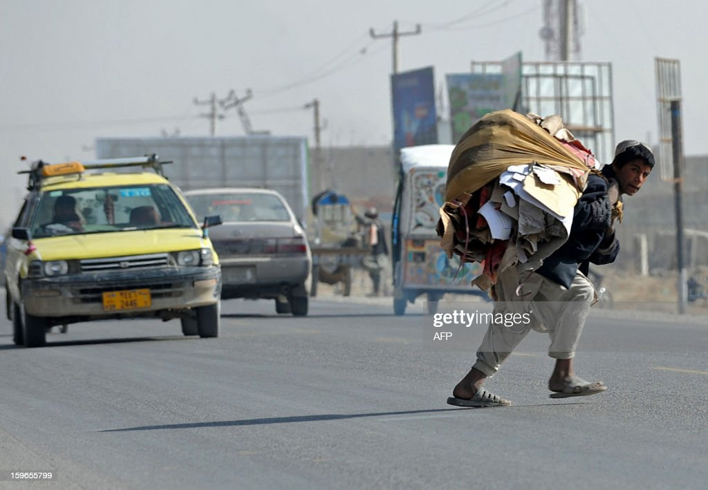 An Afghan youth carries discarded cardboard to be used as fuel as he crosses a street in Kandahar on January 17, 2013. Over a third of Afghans are living in abject poverty, as those in power are more concerned about addressing their vested interests rather than the basic needs of the population, a UN report said.