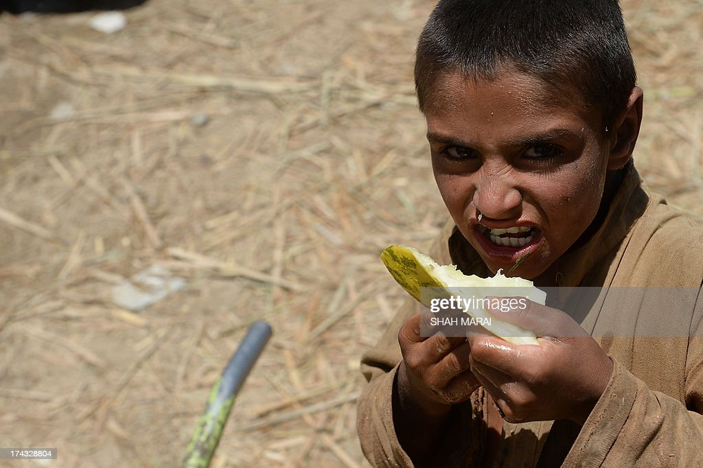 An Afghan youth eats a piece of spoiled melon at a fruit market in Kabul on July 24, 2013, during the holy month of Ramadan. Throughout the month, devout Muslims must abstain from food and drink from dawn until sunset when they break the fast with the Iftar meal. AFP PHOTO/ SHAH Marai
