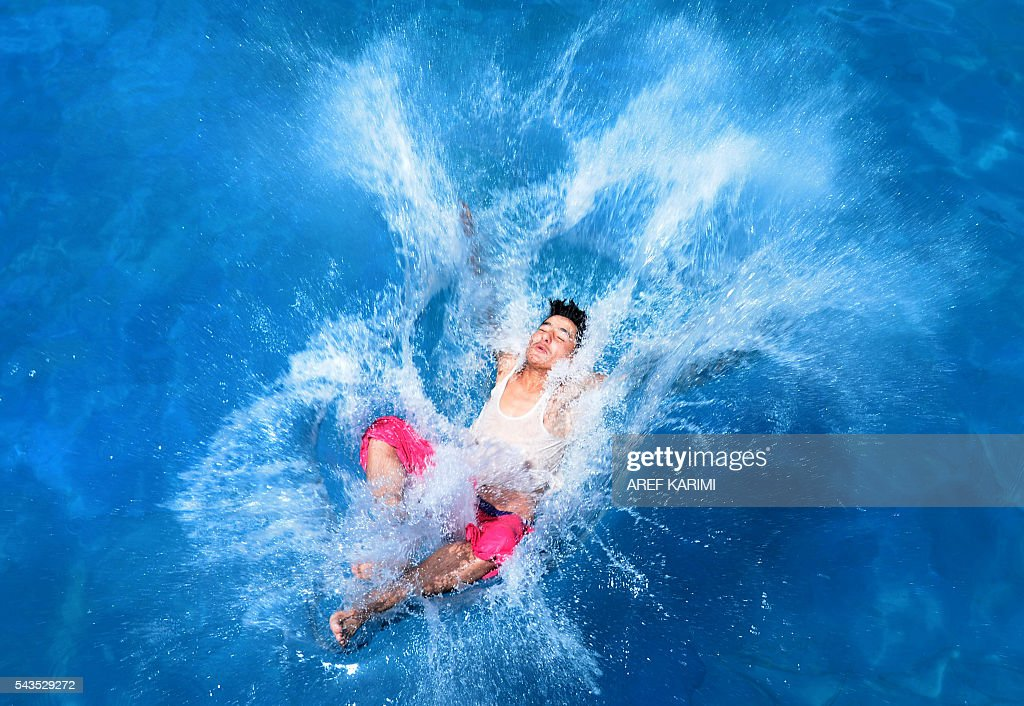 An Afghan youth jumps into a swimming pool in Herat on June 29, 2016. / AFP / AREF
