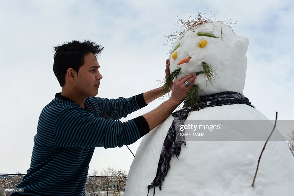 An Afghan youth makes a snowman in Kabul on February 4, 2013. As winter sets in across Central Asia, many Afghans struggle to provide adequate food and shelter for their families. AFP PHOTO/ SHAH Marai