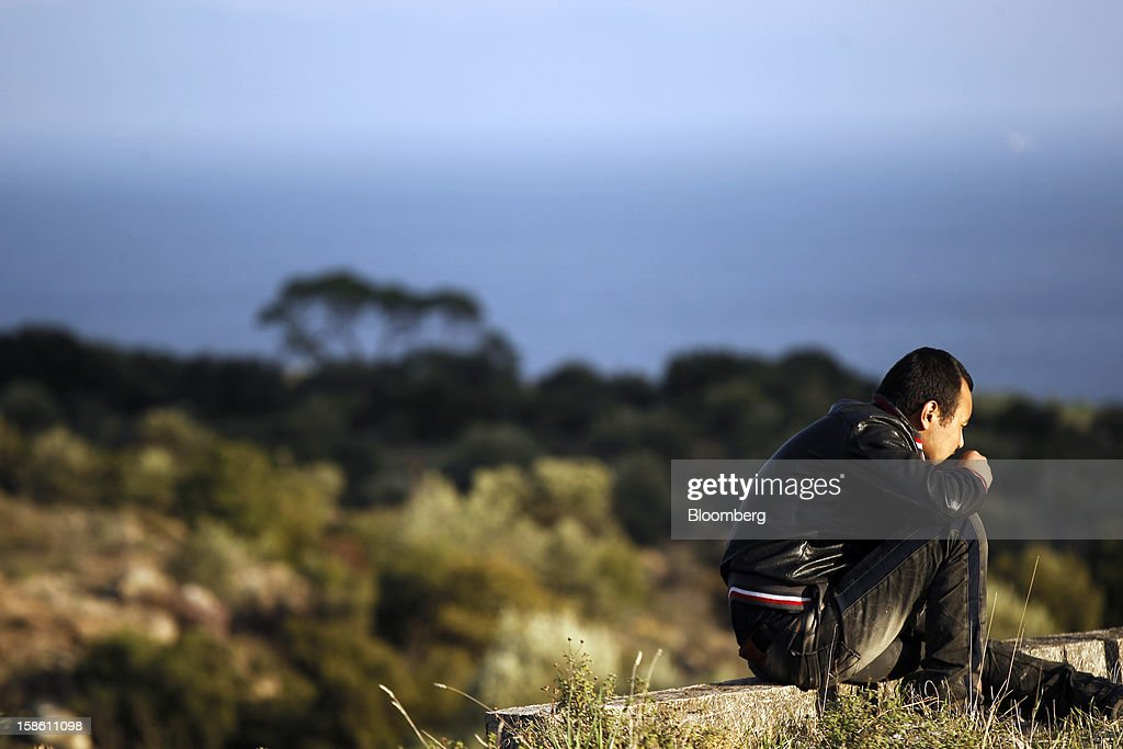 An Afghan youth rests on a roadside after leaving Mantamados to walk to the town of Mytilene hours after arriving by boat from Turkey in the northern part of the island of Lesbos, Greece, on Saturday, Dec. 8, 2012. In recent months, Lesbos has become a hot spot for migrants as Greece struggles to cope with waves of refugees from Middle Eastern conflict even as it reels from economic crisis at home. Photographer: Kostas Tsironis/Bloomberg via Getty Images