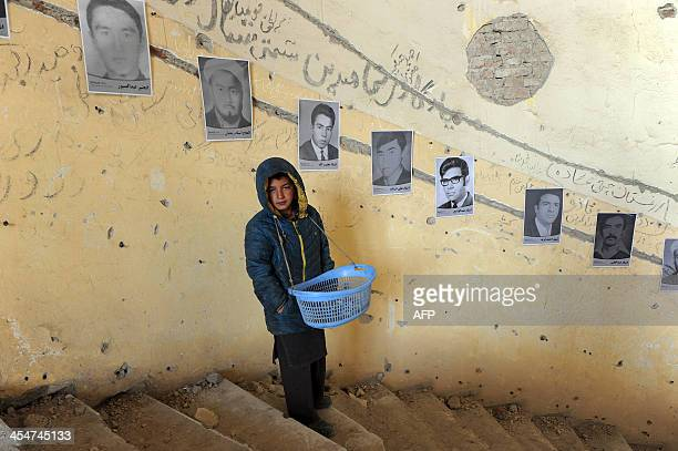 An Afghan youth stands alongside photographs of victims of war on display to mark Human Rights day at the ruined Darlaman Palace in Kabul on December...