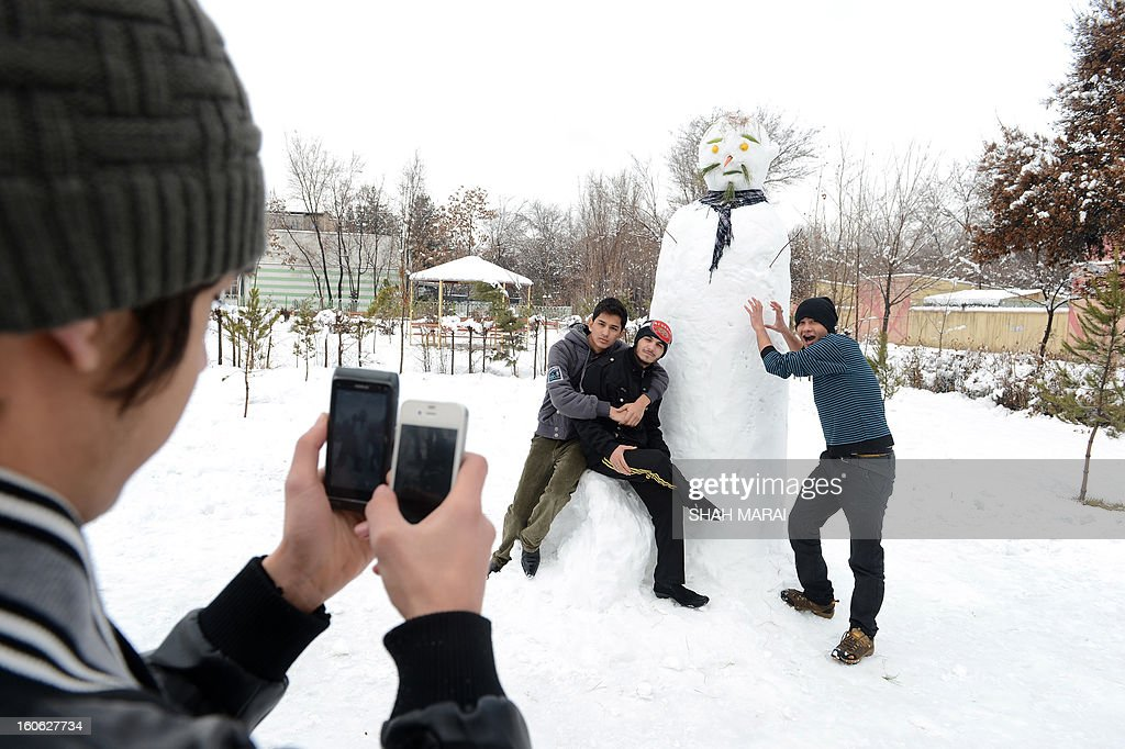 An Afghan youth takes mobile phone pictures of his friends posing with a snowman in Kabul on February 4, 2013. As winter sets in across Central Asia, many Afghans struggle to provide adequate food and shelter for their families. AFP PHOTO/ SHAH Marai