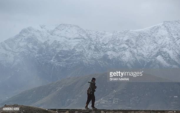 An Afghan youth walks in front of snow covered mountains on a hilltop overlooking Kabul on February 3 2014 The harsh Afghan winters lasting from...