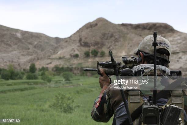 An Afghani soldier aims with his weapon during a military operation against Daesh terrorists in the Nangarhar province of Afghanistan bordering...