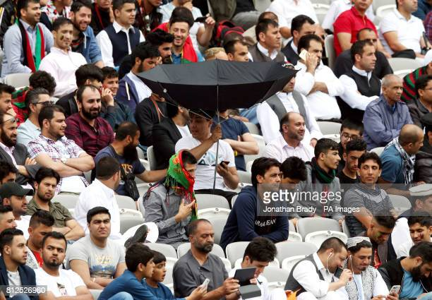 An Afghanistan cricket fan holds his umbrella upside down in the stands during the one day match at Lord's London
