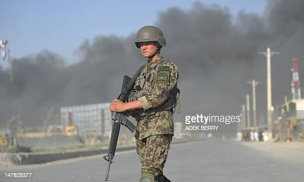 An Afghanistan National Army soldiers stands guard at the scene following an explosion at a fuel warehouse in Kabul on July 4 2012 A huge explosion...