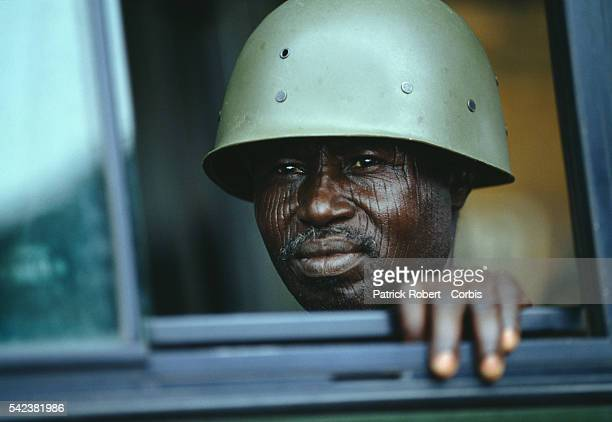 An AFL soldier with tribal facial scars looks through a window in Schieffelin during the Liberian Civil War AFL forces under pressure from Ghanaian...