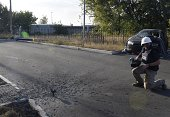 An AFP cameraman readies to film as shell that struck along a road close to Donetsk's International Airport as shelling continues between proRussian...