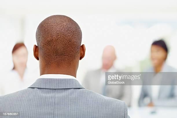 Eine afrikanische amerikanische Geschäftsmann und sein team im Hintergrund