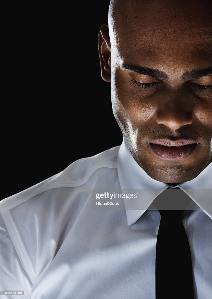 An African American business man with eyes closed against black
