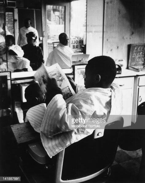 ... newspaper seated in a barbers chair in Harlem New York February 1956