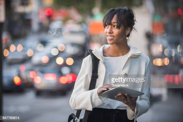 An African American female Millennial in business attire with a mobile device walking the streets of Downtown Los Angeles