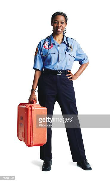 an african american female paramedic stands in uniform holding her gear