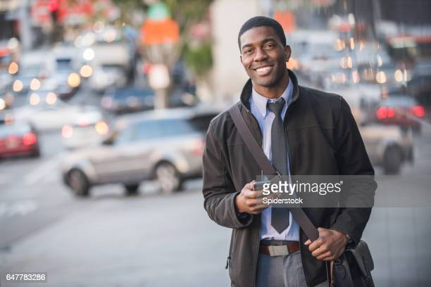 An African American male Millennial in business attire with a smartphone walking the streets of Downtown Los Angeles