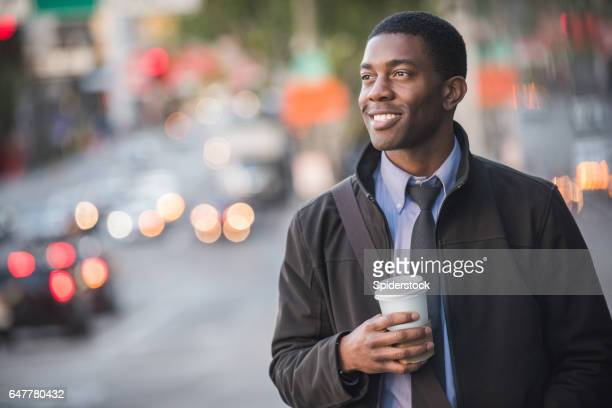 An African American male Millennial in business attire with coffee walking the streets of Downtown Los Angeles